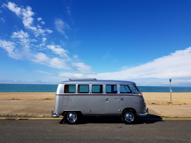 Split screen VW hearse by the sea